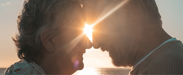 Senior couple behind a sunset