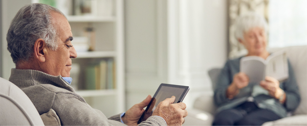 Elderly couple reading a book and a tablet