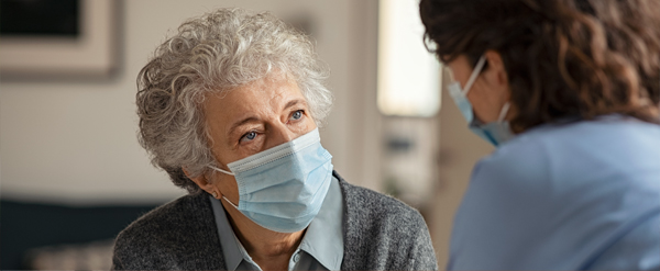Senior lady and nurse talking while wearing medical masks
