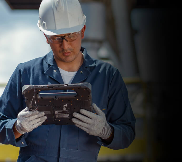Outdoor field worker wearing hard hat and PPE looking at screen of Zebra tablet