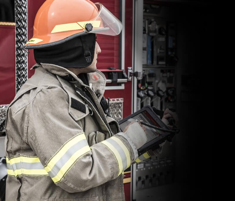 Firefighter sitting down looking at tablet