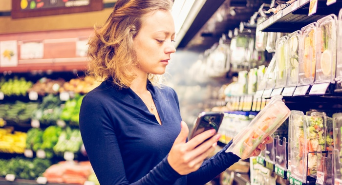 Woman in grocery store holding device and salad
