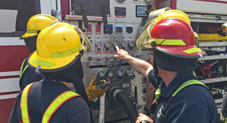 Four firefighters stand facing a fire engine, while one holds a Zebra mobile computer.