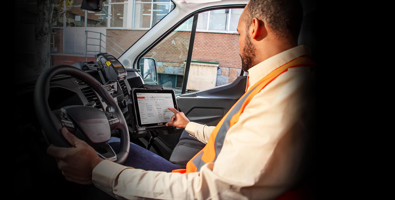 Service technician inside vehicle operating Zebra tablet next to him