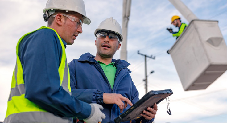 Two utility workers stand in the foreground, one holds a Zebra rugged tablet.