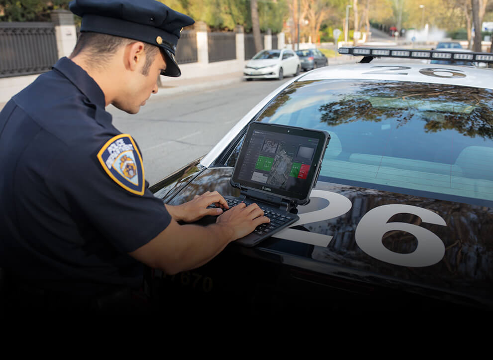 Police officer using Zebra's Rugged Tablet on the back of his squad car